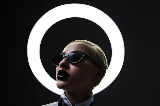 Портрет модная блондинка носить черные очки и черные губы молиться. круглая лампочка Premium Фотографии
