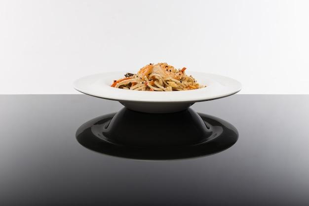 Лапша с морепродуктами на черном столе с белым Premium Фотографии