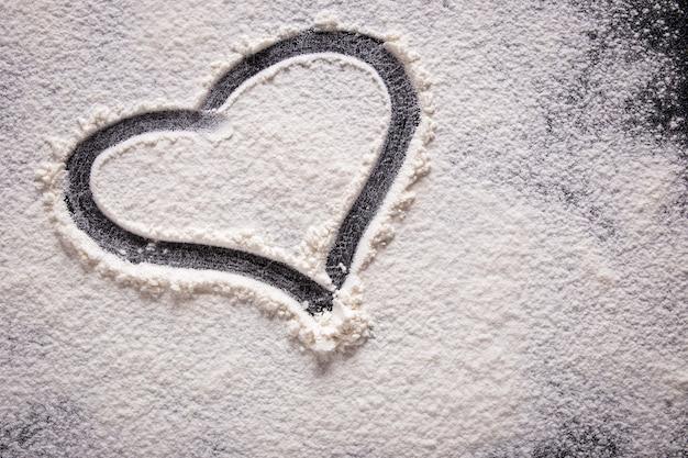Форма сердца нарисованная на муке на черной предпосылке. крупный план. Premium Фотографии