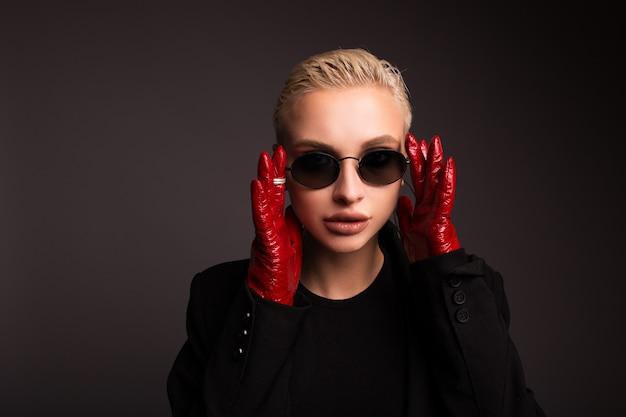 孤立した灰色の背景に赤い革手袋とスタイリッシュなブロンドの肖像画。大きなリングの形のイヤリング。積極的なスタイルの女の子。 Premium写真
