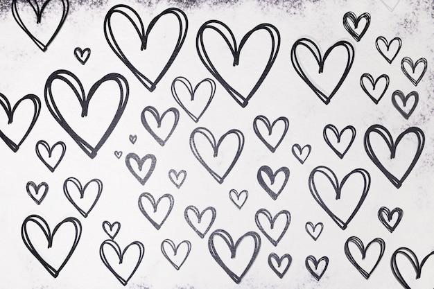 Текстура нарисованные сердца в черном на белом фоне из муки. день святого валентина. Premium Фотографии