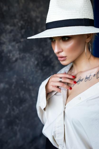 Красивая блондинка в белой рубашке с черными брюками и белой шляпе на синей стене Premium Фотографии