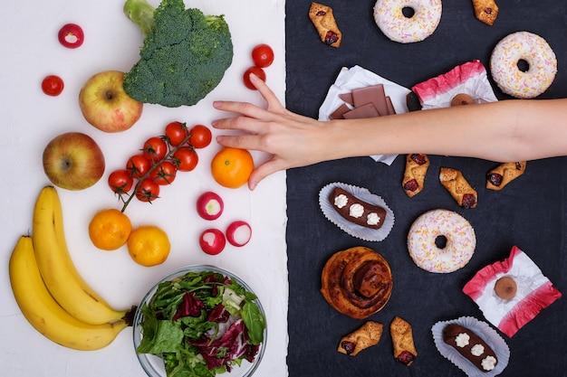Фрукты и овощи против пончиков, сладостей и гамбургеров Premium Фотографии