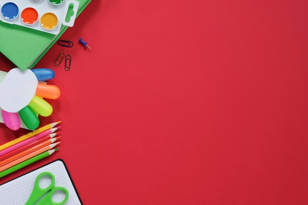 様々な学用品や赤の背景に文房具のレイアウト。 Premium写真