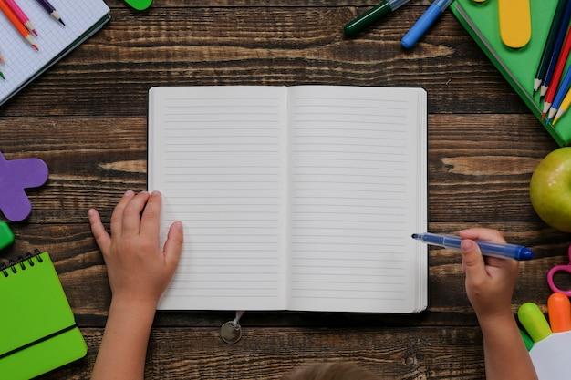 木製のテーブルに子供の手でさまざまな学用品や文房具のレイアウト。 Premium写真