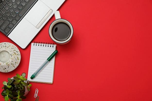 Плоский лежал современный рабочий стол красный стол с ноутбуком, очки, смартфон, чашка кофе. Premium Фотографии