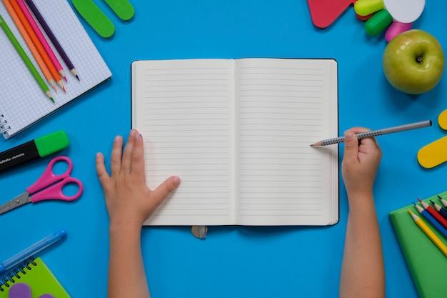 さまざまな学用品や子供の手を使った文房具のレイアウト Premium写真