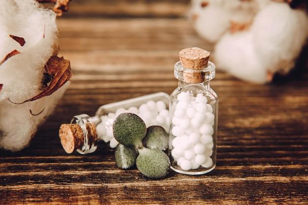 ホメオパシーの小球とガラス瓶は木の表面にクローズアップ。 Premium写真