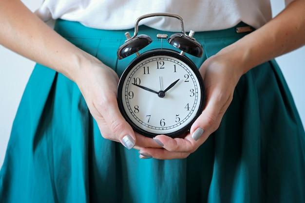 Женщина, держащая часы на живот. пропущенный период, нежелательная беременность, здоровье женщины и задержка менструации. Premium Фотографии