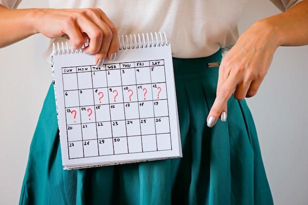 欠落した期間とカレンダー上のマーキング。望まない妊娠と月経の遅れ。 Premium写真