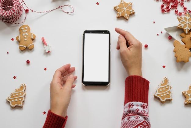 新年とクリスマスの買い物。赤い装飾が施された白いテーブルの上の電話 Premium写真