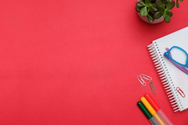 オフィスの文房具とフラットレイアウトワークスペース赤いデスク。ビジネス女性ブログヒーローコンセプト。 Premium写真