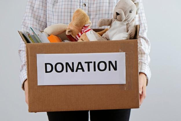 寄付のコンセプト。本やおもちゃでいっぱいの箱を持って男。子供のために寄付してください Premium写真
