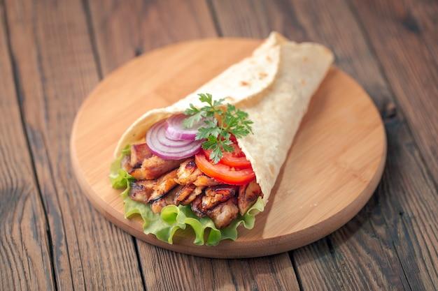 ドネルケバブはまな板の上に横たわっています。鶏肉、玉ねぎ、サラダとシャワルマは暗い古い木製のテーブルにあります。 Premium写真