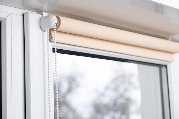 Бежевые светонепроницаемые шторки на белом пластиковом окне. жалюзи на пластиковые окна. Premium Фотографии