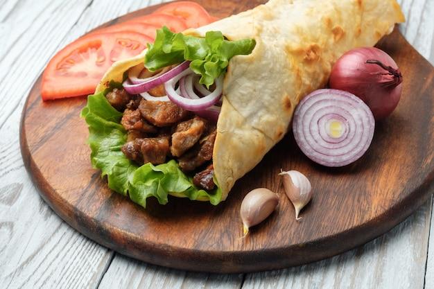 ドネルケバブはまな板の上に横たわっています。肉、玉ねぎ、サラダとシャワルマは白い古い木製のテーブルにあります。 Premium写真