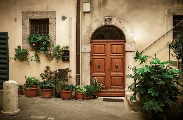 古いドアと植木鉢のあるイタリアの中庭のパティオ Premium写真
