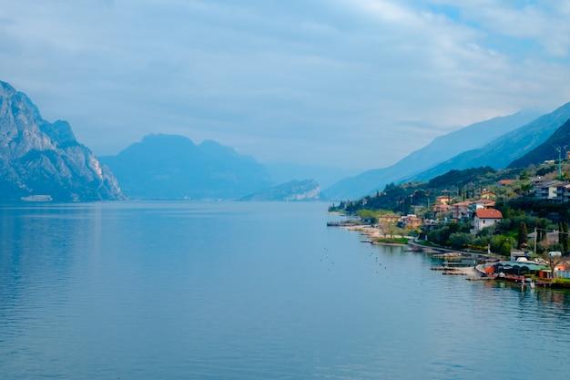 マルチェージネの町の塔からガルダ湖の眺め。イタリア。イタリアの都市の瓦屋根の眺め。ガルダ湖。リーヴァ・デル・ガルダ。 Premium写真