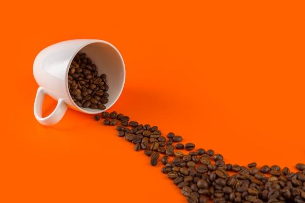 Кофе в белой чашке на оранжевом фоне с кофейными зернами. Premium Фотографии