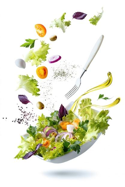 Белая тарелка с салатом и плавающими в воздухе ингредиентами: оливки, салат, лук, помидор, сыр моцарелла, петрушка, базилик и оливковое масло. Premium Фотографии