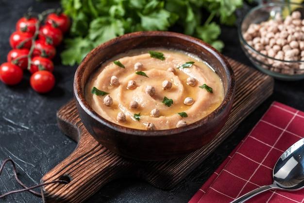 Хумус в коричневую деревянную тарелку. Premium Фотографии