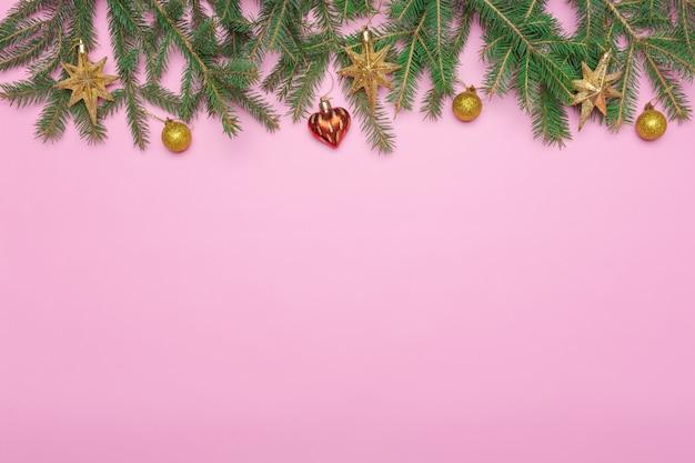 モミの枝とピンクの背景のクリスマスの装飾の休日フレーム Premium写真