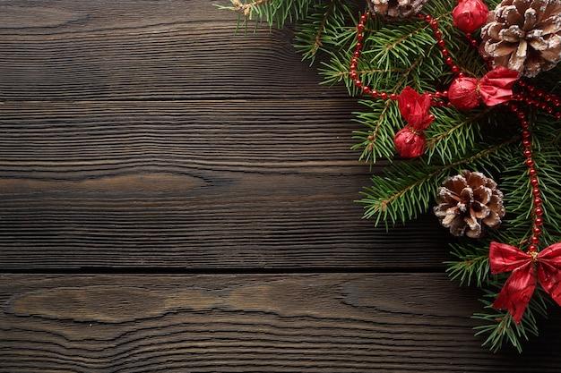 松の枝や松ぼっくりとダークウッドのテーブル 無料写真