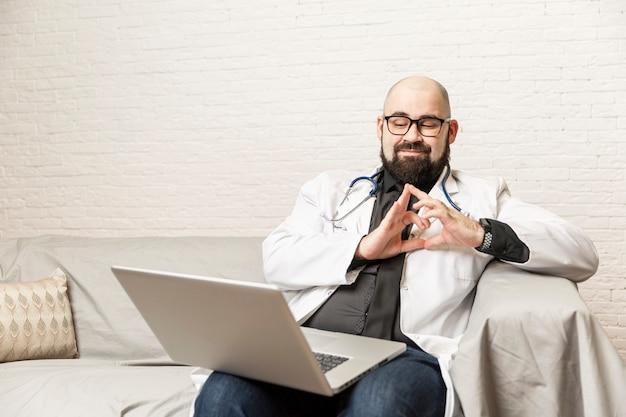 Мужской доктор сидит на диване и работает перед ноутбуком. удаленная работа, онлайн-консультации во время эпидемии. Premium Фотографии