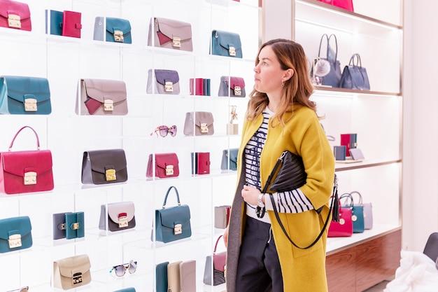 明るいコートを着た若い女性が店でバッグを選びます。ファッションアクセサリーの豊富な品揃え。 Premium写真