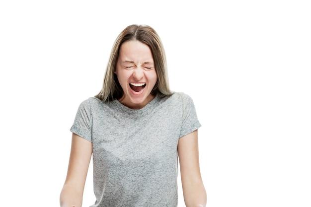 Молодая девушка кричит эмоционально. изолированные на белой стене. гнев и обида. Premium Фотографии