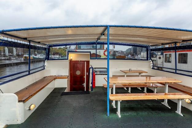 Столы со скамейками на корме гостиничного корабля в амстердаме. место для отдыха пассажиров клиентов. Premium Фотографии