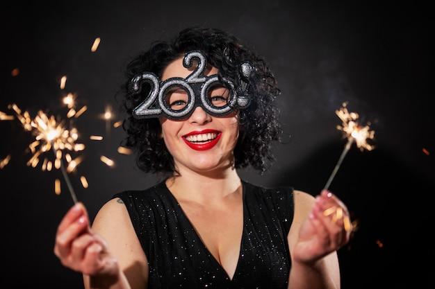 花火を持つ若い笑う女性。巻き毛のブルネット。新年のお祝い。 Premium写真
