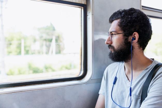Молодой человек в очках, наушниках и бороде сидит в вагоне и слушает музыку. туризм и путешествия. крупный план. Premium Фотографии