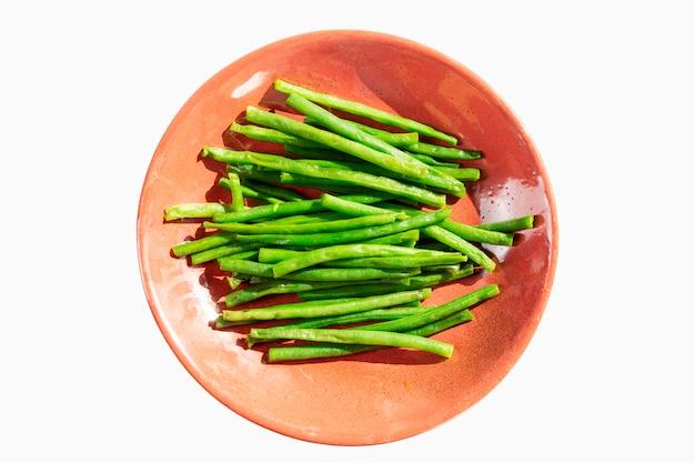 ピンクのプレート上のインゲン。ダイエット菜食。 Premium写真