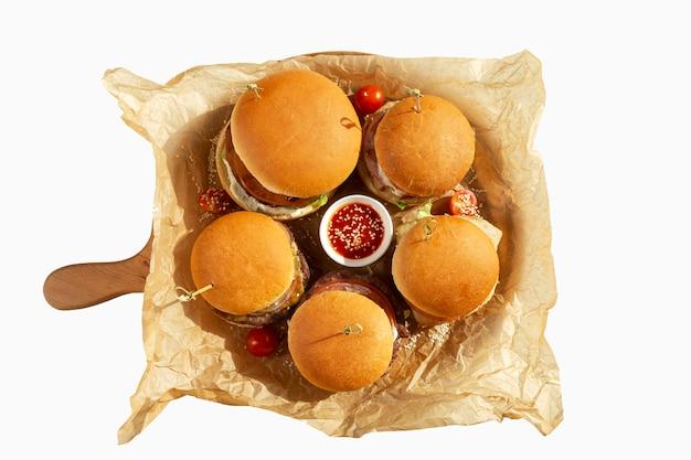 Ассорти из гамбургеров с томатным соусом на деревянной доске. вид сверху. изолированный над белизной. Premium Фотографии