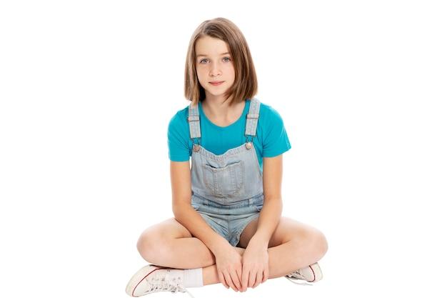 Симпатичный подросток, девушка сидит. отдельный на белом фоне. Premium Фотографии