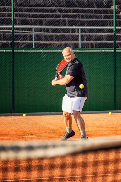 中年のハゲ男がコートで感情的にテニスをしています。アウトドア Premium写真