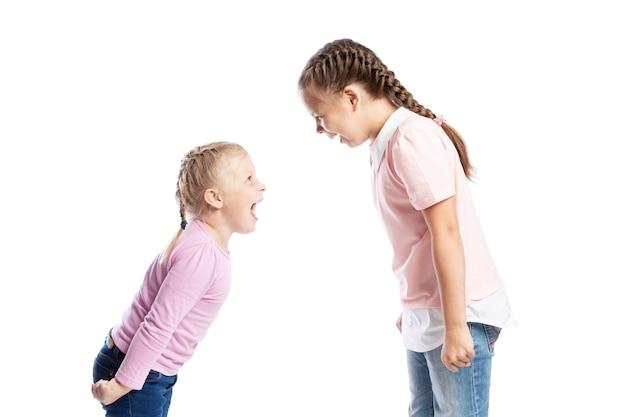 Маленькие дети, подруги в розовых свитерах и джинсах кричат друг на друга. гнев и стресс. изолированные на белом фоне. Premium Фотографии