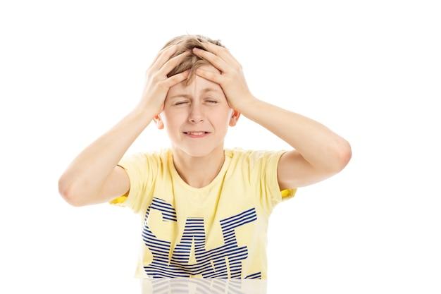 Подросток парень кричал сердито, сидя за столом. изолированные на белом фоне. Premium Фотографии