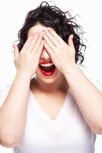 若い女の子は、彼女の手で目を閉じて笑います。白い壁。閉じる。 Premium写真
