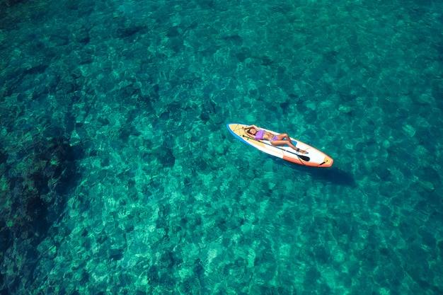 サーフボードでビキニで横たわっている間ポーズ美しいボディとセクシーな笑みを浮かべて少女 Premium写真