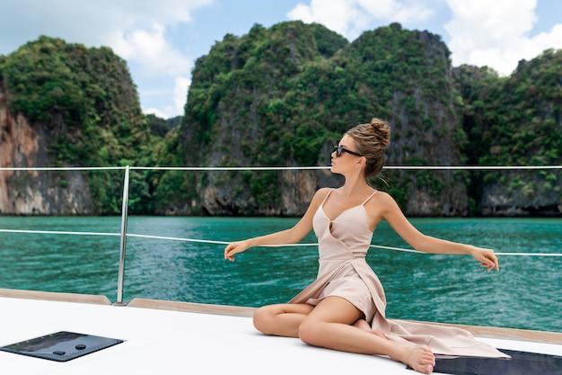 Открытый выстрел очаровательны молодой женщины в бежевом платье, стоя на краю яхты Premium Фотографии