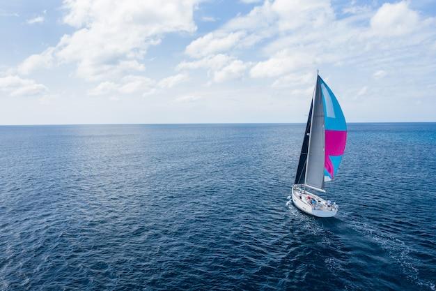 海で白い帆船ヨット。ヨットの空中ドローンビュー Premium写真