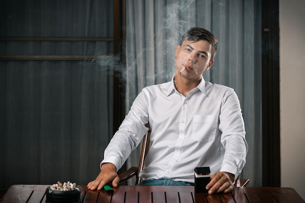 Портрет парня, позирующего сидя за столом, на котором стоит пепельница, полная сигарет Premium Фотографии