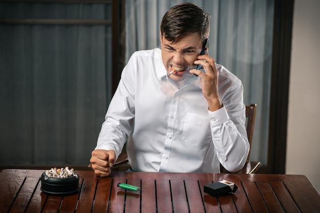 Плохие привычки. портрет парня в ярости, позирует сидя за столом Premium Фотографии