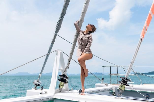 ヨットの端に立っているベージュのドレスで愛らしい若い女性の屋外撮影 Premium写真