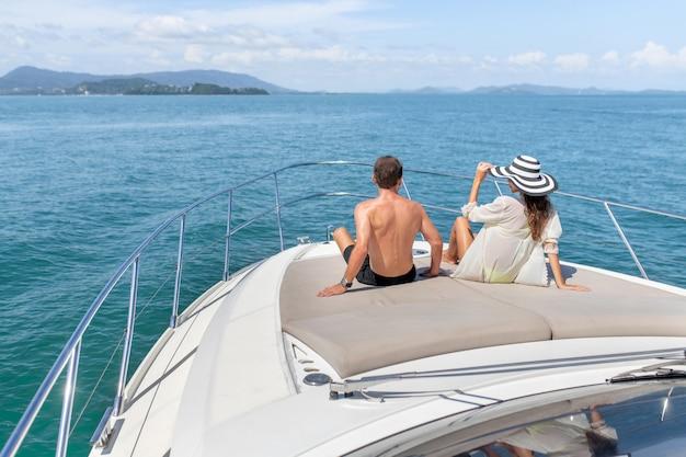 背面図:男と女は豪華な白いヨットで日光浴します。 Premium写真