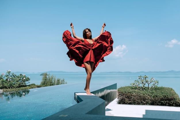 海を望むインフィニティスイミングプールの端に立っているファッション赤いドレスの女性モデル。 Premium写真