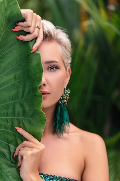 植物でふざけてポーズ青い瞳の女の子のクローズアップの肖像画。緑の葉の後ろに顔を隠す魅力的な内気な金髪女性の写真。 Premium写真