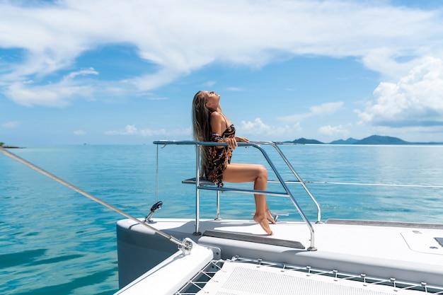 セクシーな若い女の子は、日当たりの良い、豪華な白いヨットのデッキの端に座っています。海の風景を背景に。タン自然の楽しさ。豊かな休暇。 Premium写真